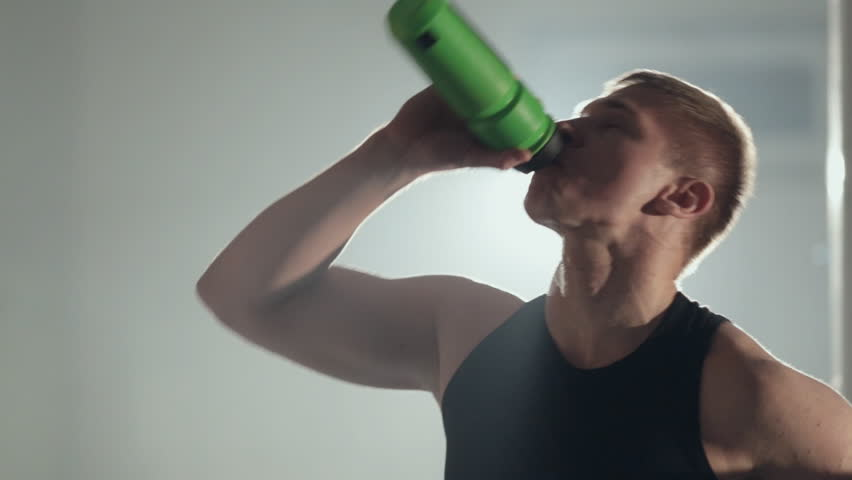 Young man drinking water after workout at the gym