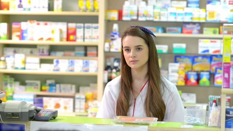 Young female pharmacist holding a receipt and selling medicine to  customer in a drugstore