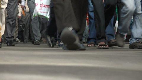 MUMBAI, INDIA - 6 NOVEMBER 2014: Train passengers exit a commuter train and walk across a platform in the Victoria Terminus in Mumbai.