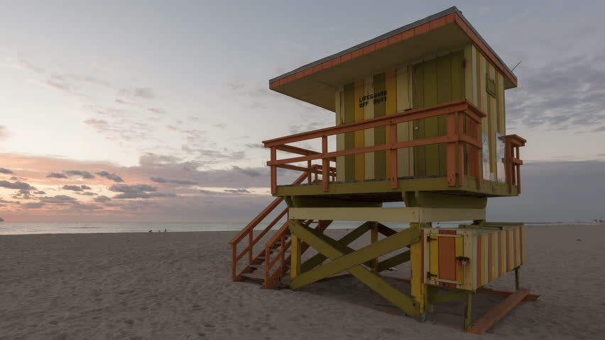 4K Time lapsepan shot Miami Beach Florida sunrise with colorful lifeguard house in typical Art Deco architecture on a summer morning with clouds and a blue sky