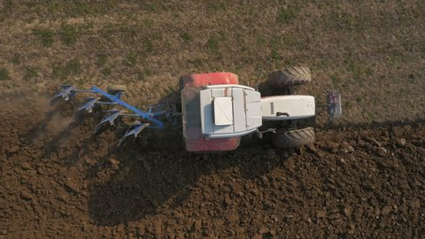 Aerial, vertical - Tractor with four furrow plough plowing a field