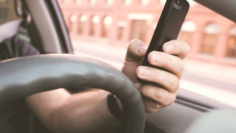 Distracted driver texting while driving through city traffic