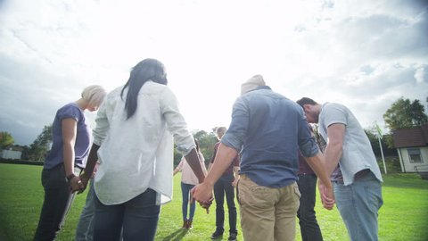 4K Happy Christian friends outdoors holding hands in a circle & bowing heads to pray