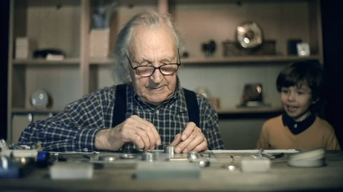 Slow motion of clock master at work, his little grandson watching him mending mechanism