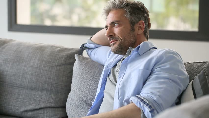 Mature man sitting in sofa and answering the phone