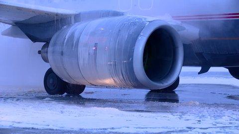 AUSTRIA, INNSBRUCK - FEBRUARY 10, 2012:Flugzeugenteisung, aircraft de-icing, defrosting with antifreeze before takeoff during strong blizzard, Innsbruck Airport