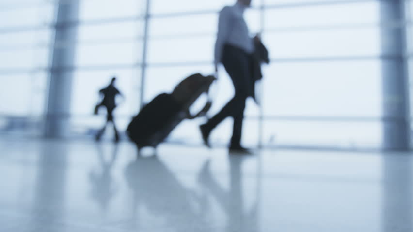 Business trip man and people on travel in airport walking with luggage and baggage going traveling with plane. Out of focus blurry background. RED EPIC SLOW MOTION FOOTAGE.