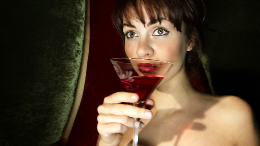 beautiful classic pinup girl in a VIP club drinking a cocktail