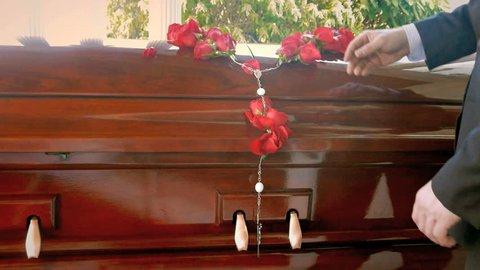 Casket at funeral service ceremony, remembrance roses fall in slow motion on coffin