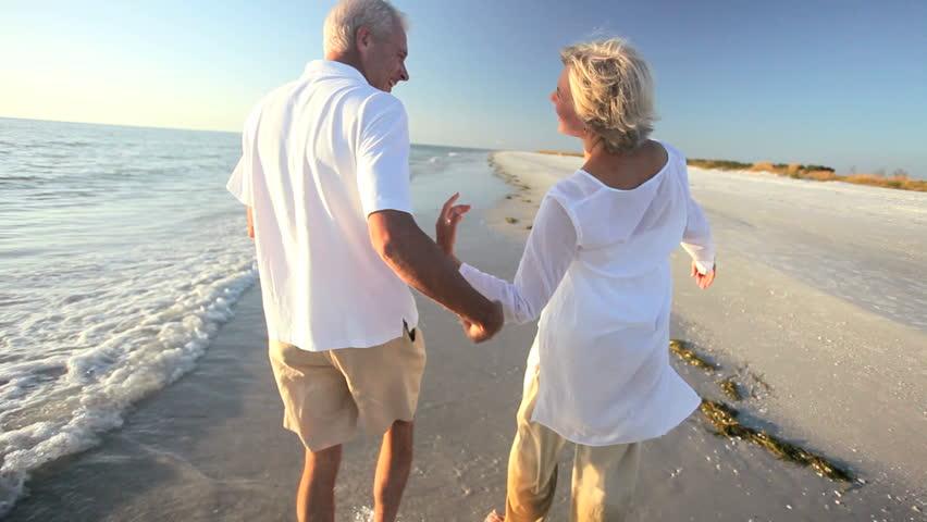 Healthy romantic senior couple dancing on the beach & enjoying a carefree lifestyle