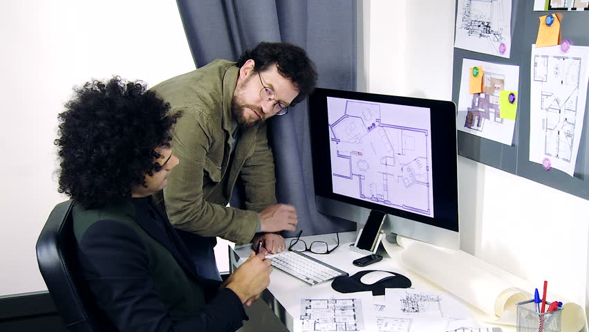 Male Interior Designers At Work three architects discussing projects at work in office medium shot
