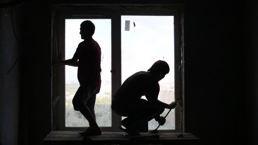 Silhouettes of two workers who dismantle old window frame. | Shutterstock HD Video #9699506