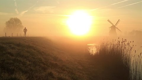 Man running on a gravel road during a foggy, spring sunrise in the Dutch countryside.
