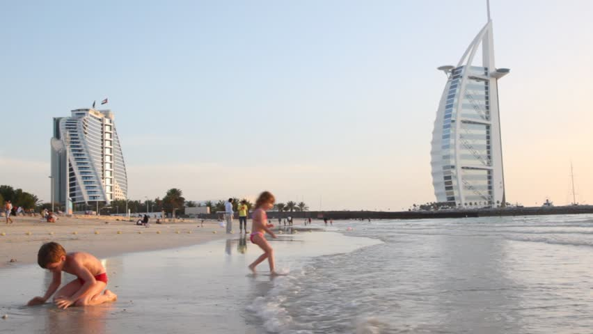 man walking along the beach in front and the burj al arab hotel