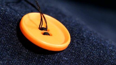 Sewing an orange button on dark jeans, denim, with black thread, close up