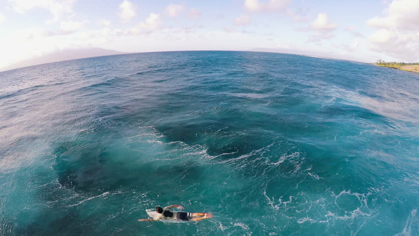 A Surfer Paddles Out Looking For Waves in a Tropical Ocean