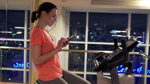 Young woman with smartphone riding stationary bike in gym at night