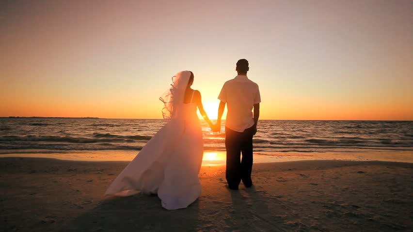 Attractive couple exchanging a kiss after their sunset wedding