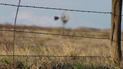 4k Video of an old Windmill focus pull from barbed wire fence, slow motion, wind blowing the grass in the desert of New Mexico