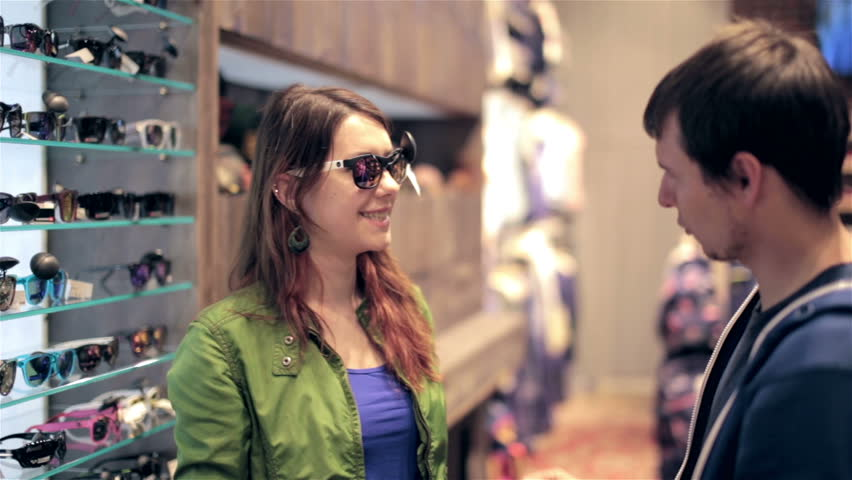 Young couple shopping in store, looking for sunglasses, discussing