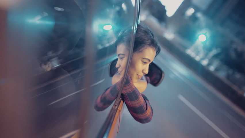 Girl leaning out of car window while driving through city streets at night