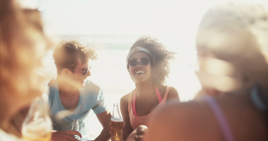 Laughing mixed racial group of friends drinking beer and relaxing together on the beach in slow motion