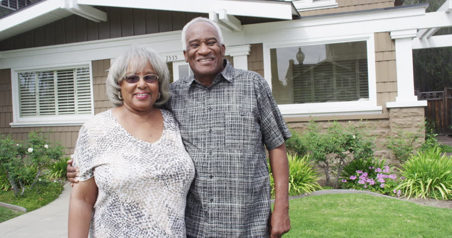 Happy senior black couple smiling in front of new home