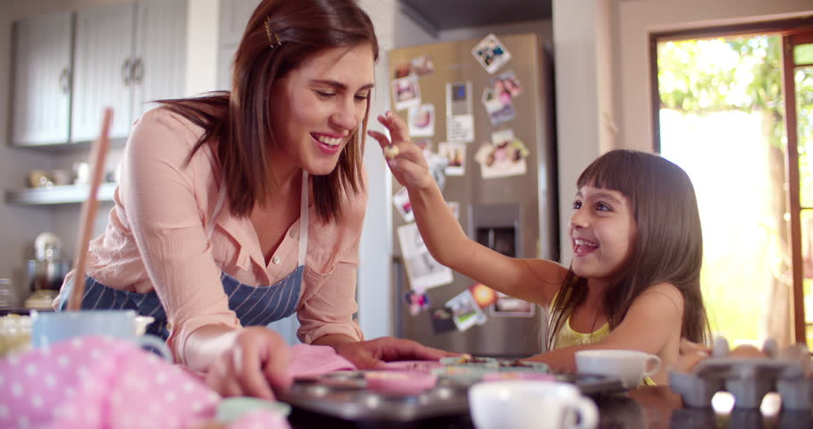 Laughing mom and daughter having fun together with the cupcake dough they are making in the kitchen while baking in Slow Motion #9791666