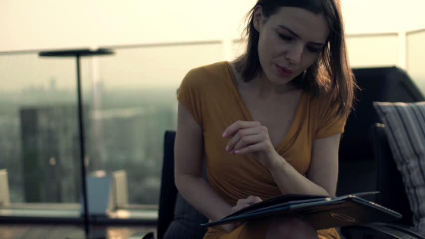 Young woman reading menu in trendy skybar  | Shutterstock HD Video #9792845
