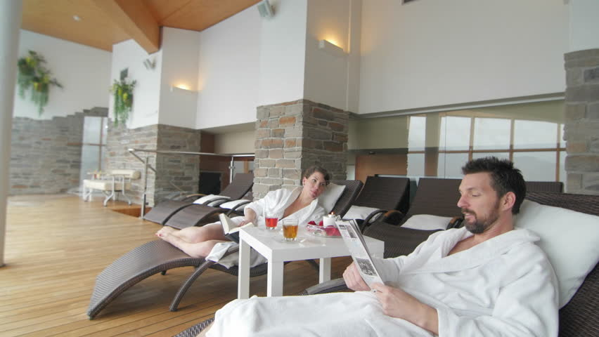 Couple relaxing and reading in the spa