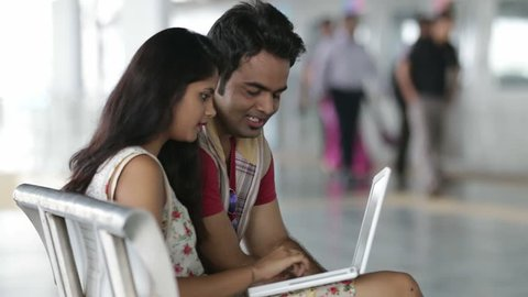 Young Indian Couple on Metro station working on lap top.