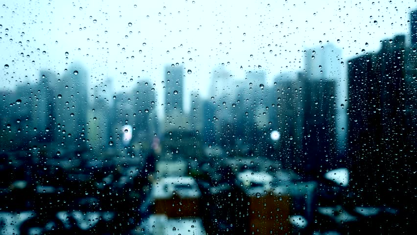 glass front window with rain drops dark moody background