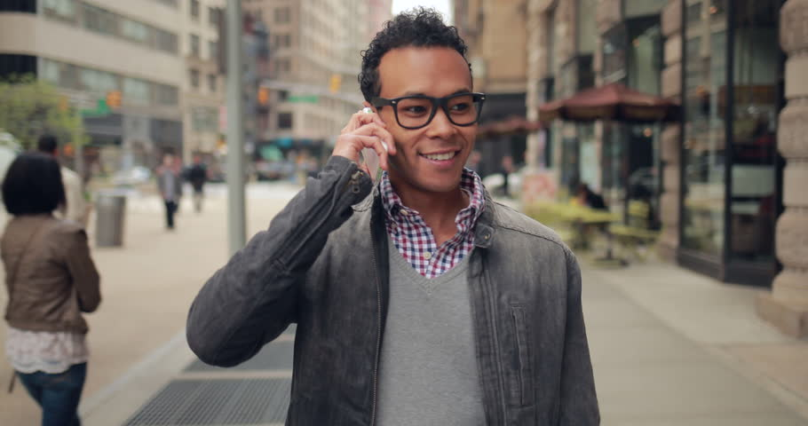 Young African Asian man in city walking talking on cell phone | Shutterstock HD Video #9925586