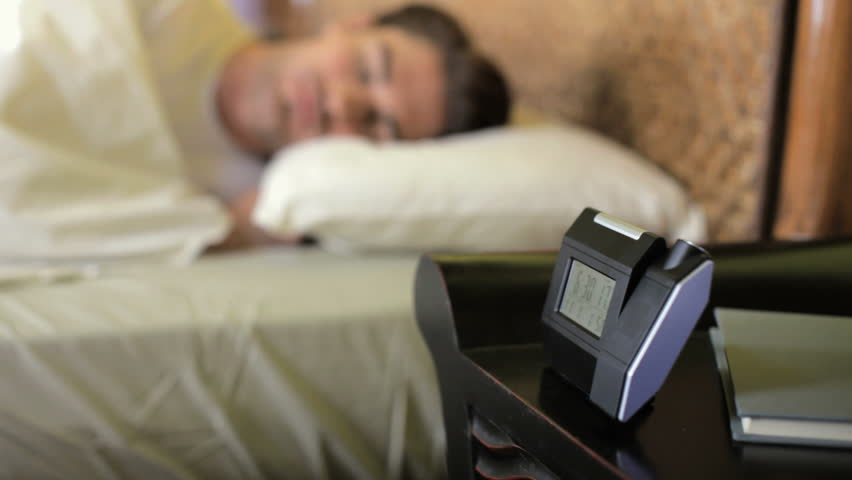Caucasian heterosexual couple in bed snoozing alarm clock. Rack focus from man to woman