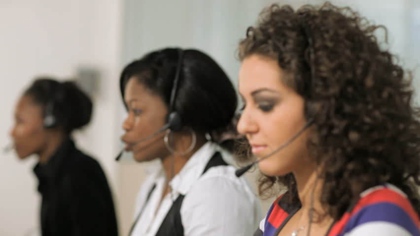 rack focus on multiethnic group of female customer service representatives talking on the phone and looking at camera.