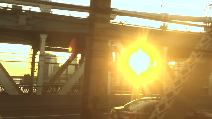 View from the window of a New York subway train traveling from Brooklyn to Manhattan with the sun setting over the city skyline