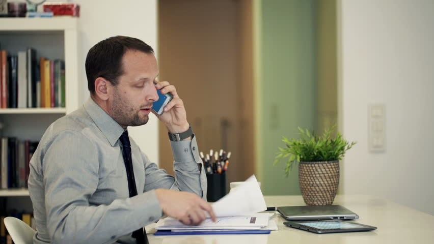Young businessman with documents and tablet computer talking on cellphone at home   | Shutterstock HD Video #9982727
