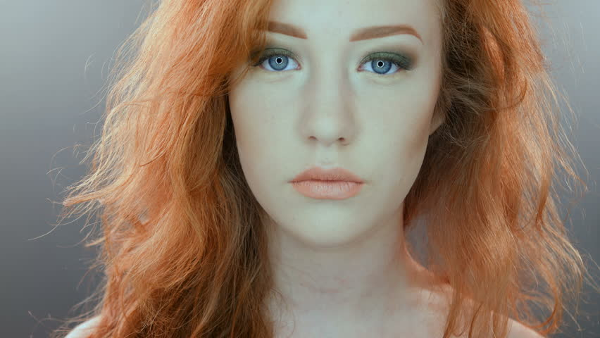 Beautiful teenage girl with red blowing hair and blue eyes on grey studio background