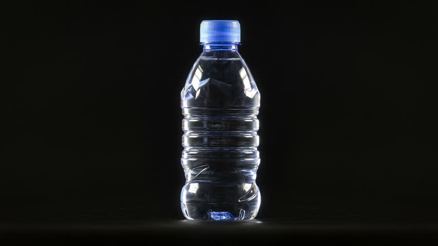 Drinking mineral water plastic bottle close up rotation on the black background 4K